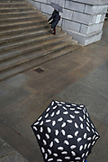 Two people carrying umbrellas in Trafalgar Square, on 29th March, 2018 in London, England.