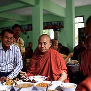 "May 14, 2013 - Mandalay, Myanmar: Ashin Wirathu (centre), the buddhist monk leader of Burma's anti-Muslim movement 969 group, takes the traditional midday meal offered by regular citizens at Mosayein Monastery in central Mandalay. Wirathu, who was jailed in 2003 for inciting religious hatred, refers to himself as ""the Burmese Bin Laden"". (Paulo Nunes dos Santos/Polaris)"