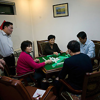 BEIJING, 25. JANUARY, 2009 :   Mr. Li's  relatives play mahjong in the basement of his apartment on new years' eve  in Beijing .<br /> Mr. Li, a paper factory owner, is facing one of his most difficult times .&quot; Last November the market suddenly went down ,&quot; Li says.   <br /> He had bought paper, a lot of paper, and paid 7000 Yuan/ t .<br />  Li's company buys paper from paper mills and lives from the sales to publishing houses and other companies.  Since the market's collapse , he manages to sell the paper only for 6000 Yuan/t.<br /> His clients' export business to the USA had shrunk in Southern China. Mobile phone manufacturers don't need paper for the instruction guides to their mobile phones anymore as their US clients buys less China- made mobile phones.<br />  Toy manufacturers don't need paper anymore  because Americans import less toys from China. &quot; The crisis has driven many of my clients into bancruptsy&quot;, says Li.<br />  <br /> China's Communist Party  which will celebrate its 60th anniversary in October, currently faces its biggest challenge since the beginning of the economic reforms 30 years ago  : &quot; The phase of  rapid economic growth is over. For the first time the government is threatened with a  mistrust of a wide section of the population&quot;, warns the Communist party's Shang Dewen in Beijing.   <br /> Not only the China's poorest worry about the furture, but as well China's middle class is concerned about the crisis.     1,5 Millionen university graduates didn't find a job until the end of 2008  and this summer there'll be an additional  6,1 Million new graduates. More than 12 percent of university graduates face unemployment in 2009.