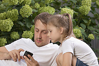 Young father sits with daughter in back garden explaining functions of his phone