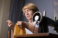 Mature woman repairing clothes