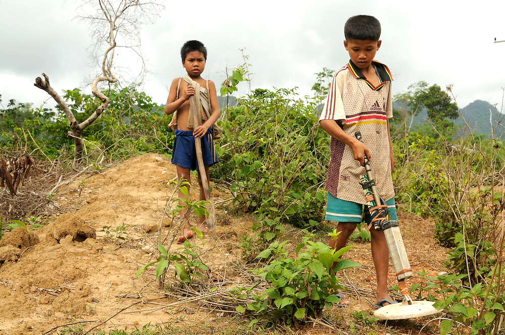 "Children search for live bombs and bomb scrap on the Ho Chi Minh Trail.  Many UXO accidents in Laos are now caused by scrap metal hunters intentionally contacting and trying to open live bombs to sell...Laos was part of a ""Secret War"", waged within its borders primarily by the USA and North Vietnam.  Many left over weapons supplied by China and Russia continue to kill.  However, between 90 and 270 million fist size cluster bombs were dropped on Laos by the USA, with a failure rate up to 30%.  Millions of live cluster bombs still contaminate large areas of Laos causing death and injury.  The US Military dropped approximately 2 million tons of bombs on Laos making it, per capita, the most heavily bombed country in the world. ..The women of Mines Advisory Group (MAG) work everyday under dangerous conditions removing unexploded ordinance (UXO) from fields and villages...***All photographs of MAG's work must include (either on the photo or right next to it) the credit as follows:  Mine clearance by MAG (Reg. charity)***."