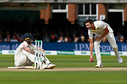 Ben Stokes of England sits on the ground after being struck in the groin by a ball bowled by Josh Hazlewood of Australia during the International Test Match 2019 match between England and Australia at Lord's Cricket Ground, St John's Wood, United Kingdom on 18 August 2019.