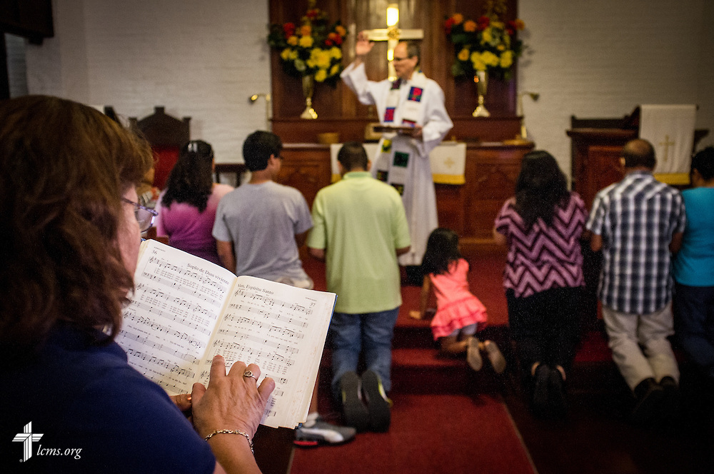 "Parishioner Maggie Salinas, a church member for about 30 years, sings hymns as she waits for other parishioners to receive Communion from the Rev. Dr. Eric Moeller at El Calvario Lutheran Church on Sunday, April 17, 2016, in Brownsville, Texas. ""Praise the Lord,"" said Salinas, who came to the church and said was blessed to have learned the Bible from teaching. ""The church has helped me in so many ways,"" said Salinas. LCMS Communications/Erik M. Lunsford"
