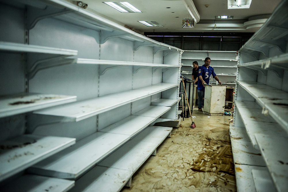 CARACAS, VENEZUELA - APRIL 21, 2017:  Gregorio Rodríguez works to clean the Ofercenter supermarket where he works, that was one of over a dozen stores looted late last night in El Valle, a working class neighborhood in Caracas. The streets of Caracas erupted into a night of riots, looting and clashes with National Guardsmen as anger from two days of pro-democracy protests spilled into unrest in working class neighborhoods and slums. Shots rang out throughout the night in El Valle, a neighborhood of mixed loyalties, as armored vehicles struggled to contain crowds of looters. At one point during the night, clashes became so heavy that a nearby children's hospital was evacuated after the ward filled with tear gas. The government said they were responding to an attack on the hospital by opposition protestors.  PHOTO: Meridith Kohut