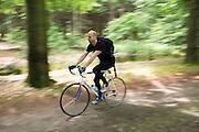 In Lage Vuursche rijdt een man op een oude Giant racefiets door het bos.<br /> <br /> In Lage Vuursche a man is cycling on a road bike in the forest.