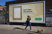 A lady walks with her small pet dog past a large billboard ad for high street opticians chain, Specsavers, on 2nd October 2019, in London, England.