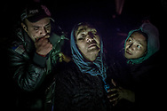 An Afghan woman is helped by relatives after arriving on a dinghy with other refugees and migrants from a Turkish coast to the northeastern Greek island of Lesbos, Sunday, Nov. 15, 2015. More than 810,000 people have crossed the Mediterranean this year, and over 200,000 in October alone. Four out of five this year have crossed from Turkey to Greece. (AP Photo/Santi Palacios)