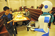 """NINGBO, CHINA - NOVEMBER 24: (CHINA OUT) <br /> <br /> Robots Act As Waiters<br /> <br /> Robots act as waiters provide service for consumers at a dinning hall at Living All square on November 24, 2014 in Ningbo, Zhejiang province of China. Lu Dike, a former e-commerce worker opened an \""""Robot Dinning Hall\"""" in which waiters were two robots. The robots can communicate basic expressions and are worked by light induced magnetic stripe. One robot costed sixty thousands and could work five years within eight hours per day after charging for four hours. The robots acting as waiters were cheaper than labor and never be tired. <br /> ©Exclusivepix"""