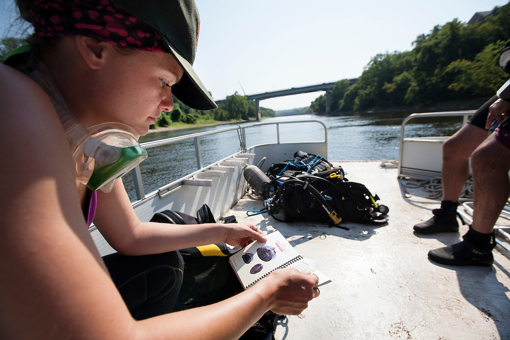 National Park Service biologist Allie Holdhusen peruses a field guide before diving for mussels in the Mississippi River August 14, 2015.