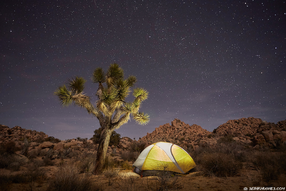 A glowing tent amidst starlight in the backcounry of Joshua Tree National Park, California.