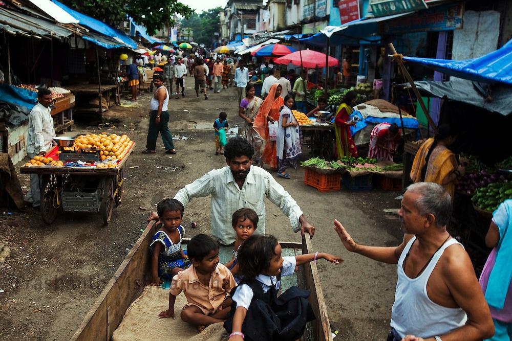 A man carts childern on a street in Dharavi , in Mumbai, India, Saturday, July, 18, 2009. Photographer: Prashanth Vishwanathan/Bloomberg
