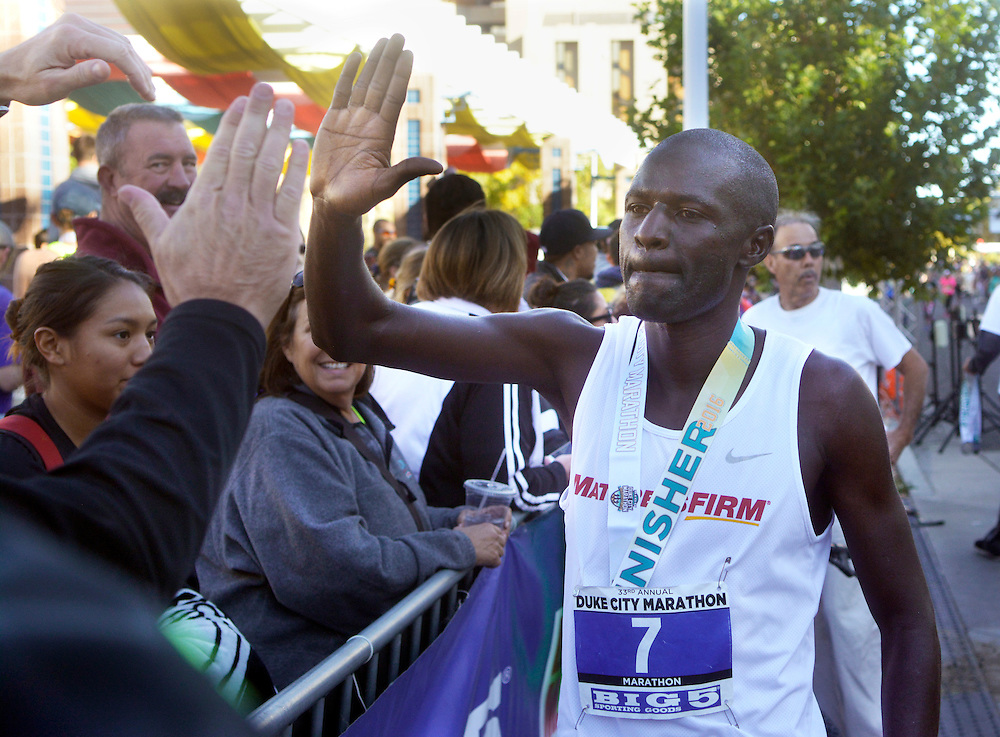 gbs101616g/SPORTS -- Solomon Kandie, men's winner of the Duke City Marathon, gets high five's from fans at the finish line on Sunday, October 16, 2016. (Greg Sorber/Albuquerque Journal)