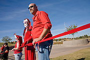 01 DECEMBER 2008 -- PHOENIX, AZ: AIDS activists in Phoenix hold a portion of the AIDS ribbon they created in a Phoenix park Monday. AIDS activists in Phoenix made the world's largest AIDS Ribbon to mark World AIDS Day, Dec. 1. According to Guinness  World Records, the previous largest AIDS ribbon measured 43 feet long. The ribbon created the Phoenix activists was more than 330 feet long. They plan to submit their ribbon to the Guinness Book of World Records.  Photo by Jack Kurtz / ZUMA Press