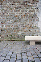 Empty stone bench against a brick wall