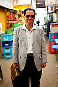 Portrait of a man with sunglasses on a market place in the center of Seoul.