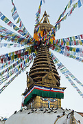 "Kathesimbhu means ""Kathmandu Swayambhu"". This 17th century stupa (bell-shaped Buddhist monument) in Kathmandu, Nepal, is a smaller version of the more famous ""Monkey Temple"" at Swayambhu. A walk around the Kathesimbhu stupa promises the old and lame the same blessings as a pilgrimage to Swayambhunath's hill. Buddha Eyes gaze from one side of Swayambhunath, the ""Monkey Temple"". On most every stupa (Buddhist shrine) in Nepal, giant Buddha Eyes (or Wisdom Eyes) stare from four sides of the upper cube. These four directions symbolize the omniscience (all-seeing) of a Buddha. The third eye (above and between the other two eyes) also symbolizes the all-seeing wisdom of the Buddha. The curled symbol (shaped like a question mark) in place of a nose is the Nepali character for the number 1, which symbolizes unity of all things. The upper part of the spire has 13 gilded disks representing the 13 steps to Buddhist enlightenment, and enlightenment is represented by an upper umbrella."