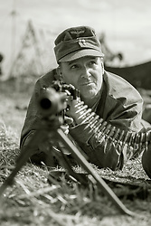 A reenactor portraying a soldier of the German Army (Heer) undergoes weapons training on the (Maschinengewehr 1942)in its Light Machine gun role. He wearing a tan and water (Stumpfuster) camouflage smock and M43 Field Cap<br /> <br />  17 July 2016<br />  Copyright Paul David Drabble<br />  www.pauldaviddrabble.photoshelter.com