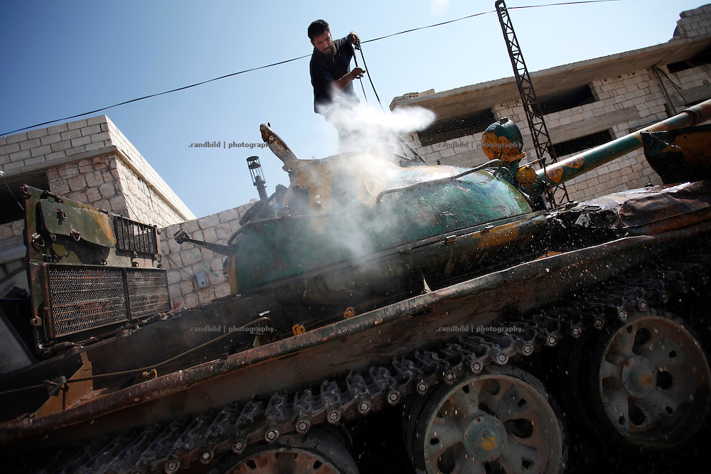 A rebel owned T-64 battle tank arrived in Koreen for maintenace and is beeing washed off its brown mud camouflage for renewal.<br /> _ _ _ <br /> Idlib Interim - Challenging life without central government in the village of Koreen (Idlib Province, Syria)<br /> Koreen joint the syrian uprisung to ouster president Bashar al-Assad at a very early stage in 2011. It has been scene of Army attacks and heavy shelling since 2012. In the course of the fightings the village of a few thousend inhabitants was almost abandoned as barrel bomb campaings commited by the regime pounded Koreen. But since regime forces retreated to few bases remaining in Idlib province people returned home to establish a new and almost unregulated economic, social and community life. The regimes power has no affect and can&acute;t reach them anymore. On the other hand a new government isn&acute;t established yet and not in sight at all. Koreen is free to make its way.