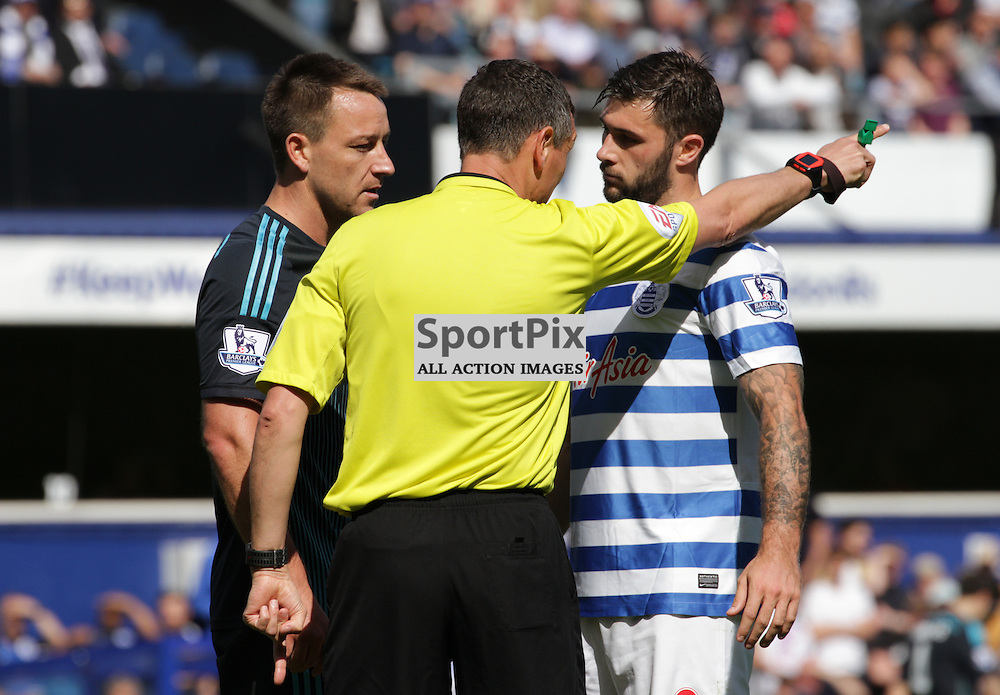 Referee Andre Marriner disciplines John Terry and Charlie Austin During the game between Queens Park Rangers and Chelsea FC on Sunday 12th April 2015