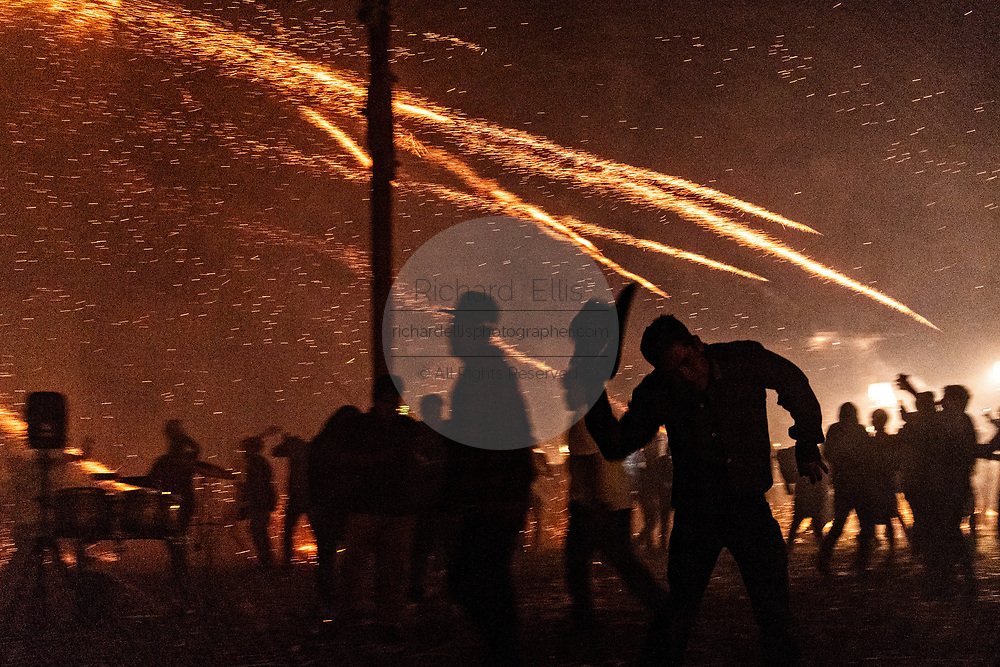 Sparks from exploding sky rockets scatter as Mexicans run for cover during a barrage of pyrotechnic rockets at the Alborada festival September 29, 2018 in San Miguel de Allende, Mexico. The unusual festival celebrates the cities patron saint with a two hour-long firework battle at 4am representing the struggle between Saint Michael and Lucifer.
