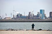 Nederland, Rotterdam, 15-9-2012Eerste maasvlakte. Op de achtergrond een raffinaderij. Een visser staat langs de nieuwe waterweg. the new land.Foto: Flip Franssen/Hollandse Hoogte