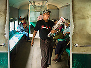 26 OCTOBER 2015 - YANGON, MYANMAR:  A newspaper vendor walks through the Yangon Circular Train. The Yangon Circular Railway is the local commuter rail network that serves the Yangon metropolitan area. Operated by Myanmar Railways, the 45.9-kilometre (28.5 mi) 39-station loop system connects satellite towns and suburban areas to the city. The railway has about 200 coaches, runs 20 times daily and sells 100,000 to 150,000 tickets daily. The loop, which takes about three hours to complete, is a popular for tourists to see a cross section of life in Yangon. The trains run from 3:45 am to 10:15 pm daily. The cost of a ticket for a distance of 15 miles is ten kyats (~nine US cents), and for over 15 miles is twenty kyats (~18 US cents).    PHOTO BY JACK KURTZ