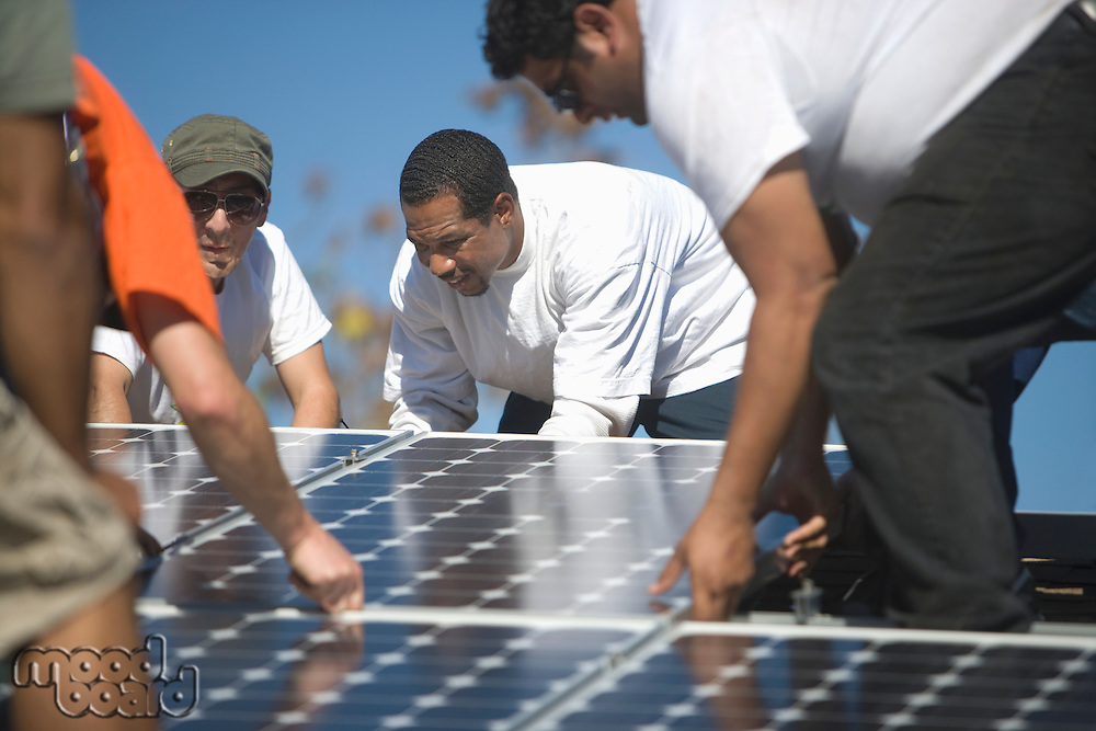 A group of men laying down a large solar panel