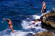 Kids jumping off rocks into the sea, Cuba