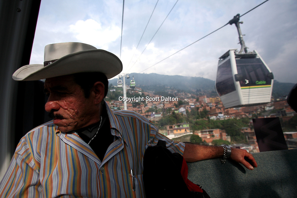 A man rides the Metro Cable that carries passengers to and from their hillside barrios to the metro rail station down in the valley in Medellin on Thursday, April 26, 2007. (Photo/Scott Dalton)