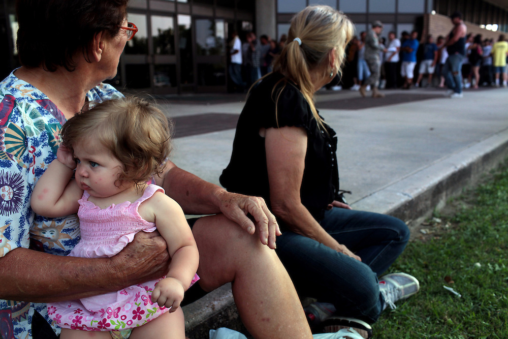 Tootsie Latapie, left, holds her great-grandaughter Mallory Battle, 11 months, beside her friend Ann Evans, right, while they wait for their husbands who were waiting in line with hundreds of fishermen for their checks from BP before the Public Meeting at the Frederick J. Sigur Civic Center Ballroom in Chalmette, Louisiana on May 24th, 2010. Over 500 fishermen and their families waited in line for over five hours in sweltering heat for their checks from BP.
