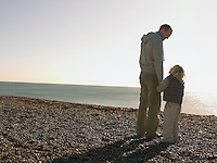 Father and son looking at each other standing on beach full length