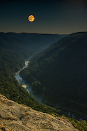The full moon rising over the New River Gorge as viewed from the Diamond Point overlook of the Endless Wall Trail, West Virginia.