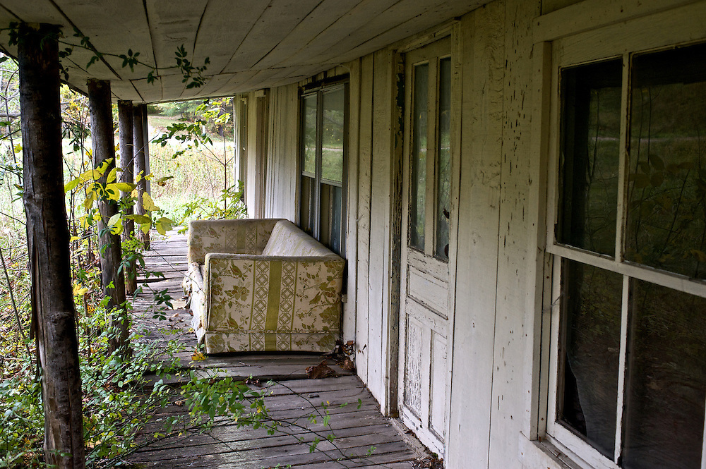 An  old couch sits on the front porch of an old North Carolina home