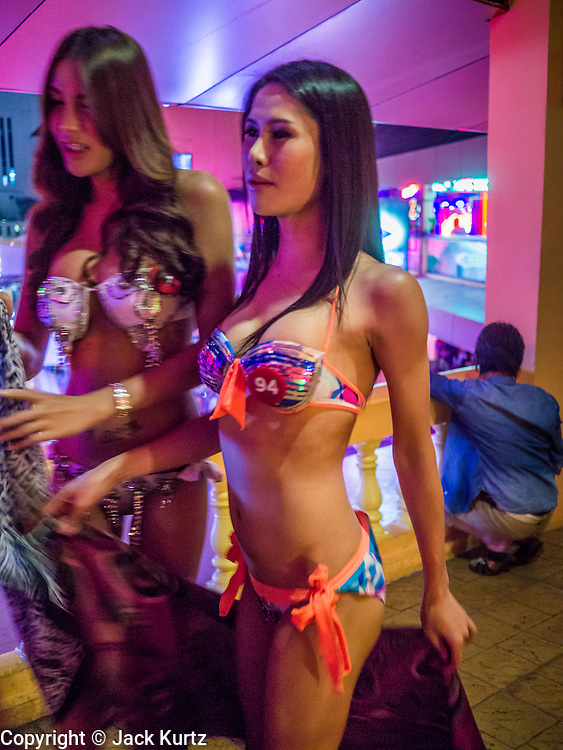 "05 JANUARY 2013 - BANGKOK, THAILAND: Sex workers solicit business and pose for photos in the Nana Entertainment District in Bangkok. Prostitution in Thailand is technically illegal, although in practice it is tolerated and partly regulated. Prostitution is practiced openly throughout the country. The number of prostitutes is difficult to determine, estimates vary widely. Since the Vietnam War, Thailand has gained international notoriety among travelers from many countries as a sex tourism destination. One estimate published in 2003 placed the trade at US$ 4.3 billion per year or about three percent of the Thai economy. It has been suggested that at least 10% of tourist dollars may be spent on the sex trade. According to a 2001 report by the World Health Organisation: ""There are between 150,000 and 200,000 sex workers (in Thailand).""      PHOTO BY JACK KURTZ"