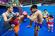 23 DECEMBER 2014 - BANGKOK, THAILAND: Boxers spar and workout in the Kanisorn gym in Bangkok. The Kanisorn boxing gym is a small gym along the Wong Wian Yai - Samut Sakhon train tracks. Young people from the nearby communities come to the gym to learn Thai boxing. Muay Thai (Muai Thai) is a mixed martial art developed in Thailand. Muay Thai became widespread internationally in the twentieth century, when Thai boxers defeated other well known boxers. A professional league is governed by the World Muay Thai Council. Muay Thai is frequently seen as a way out of poverty for young Thais. Muay Thai professionals and champions are often celebrities in Thailand.     PHOTO BY JACK KURTZ
