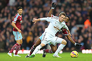 Gylfi Sigurosson of Swansea City and Alexandre Song of West Ham United fight for the ball during the Barclays Premier League match at the Boleyn Ground, London<br /> Picture by Richard Calver/Focus Images Ltd +447792 981244<br /> 07/12/2014