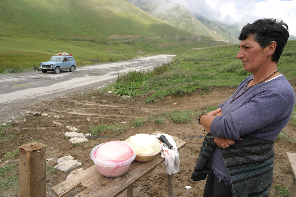 Am Kreuz-Pass (2400 m.) der Georgischen Heerstrasse verkauft eine Baeuerin selbstgemachten Kaese aus Kuhmilch an vorbeikommende. A woman offers farmers cheese at the roadside Georgian Military Highway, near the cross pass.