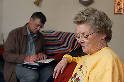 Welfare rights worker filling in form on behalf of service user during a home visit,
