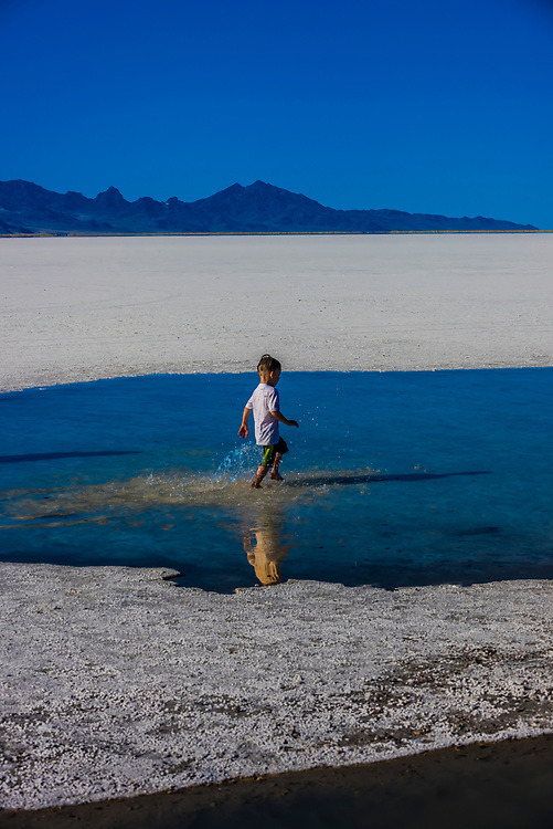 Young boy running through salty water at the Bonneville Salt Flats, Utah USA. Numerous world land speed records for autos and motorcycles have been set here.