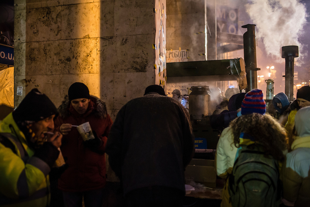 KIEV, UKRAINE - DECEMBER 11: Anti-government protesters crowd around a field kitchen offering free hot food on Independence Square, known as the Euromaidan, on December 11, 2013 in Kiev, Ukraine. Thousands of people have been protesting against the government since a decision by Ukrainian president Viktor Yanukovych to suspend a trade and partnership agreement with the European Union in favor of incentives from Russia. (Photo by Brendan Hoffman/Getty Images) *** Local Caption ***