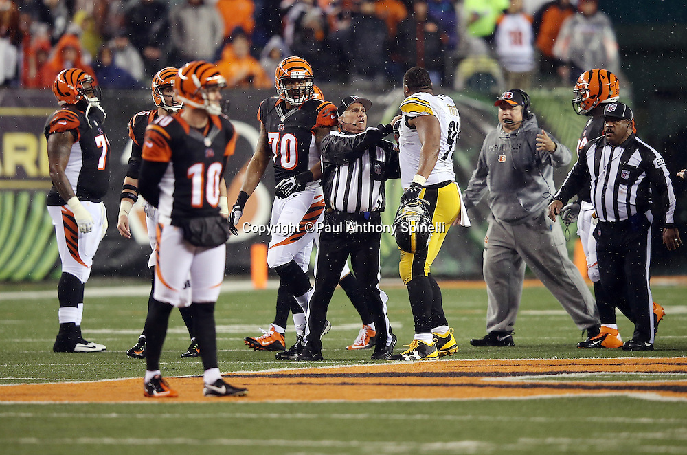 NFL back judge Perry Paganelli (46) and his crew members try to regain order and clear the field of unnecessary players and coaches after Cincinnati Bengals running back Giovani Bernard (25) gets hit hard by Pittsburgh Steelers inside linebacker Ryan Shazier (50) causing a third quarter fumble, recovered by Shazier, and starting a player melee over no penalty call for unnecessary roughness and leading with the helmet during the NFL AFC Wild Card playoff football game against the Pittsburgh Steelers on Saturday, Jan. 9, 2016 in Cincinnati. The Steelers won the game 18-16. (©Paul Anthony Spinelli)