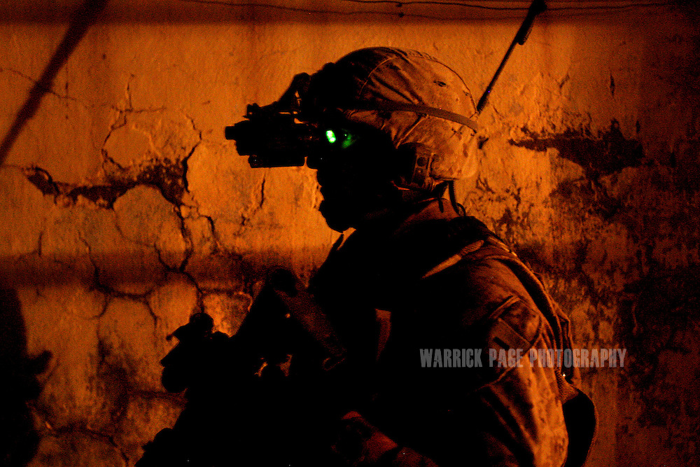 IRAQ, BASRA - JULY 4: 1st Lt. Phil Wagner, of USMC 1st Battalion 26th Brigade 2nd Division, from Ohio, monitors and alleyway with night-vision during an evening patrol in the poverty stricken neighborhood of Hayaniyah, July 4, 2008 in Basra, Iraq. When British forces withdrew in 2007, Basra deteriorated into street battles between numerous Shiite militias and criminal gangs. In April 2008, Iraqi prime minister, Nouri al Maliki, sent two Iraqi army divisions to retake control of Basra. While the fighting has ended, unemployment is rife, at about 70 per cent. Since early 2008, Iraq's security situation has improved with oil production increasing, record government surplus and easing sectarian tensions. (Photo by Warrick Page)