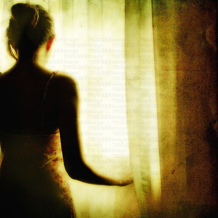 A young woman with her back to us standing at a window