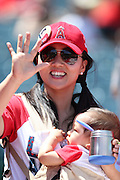 ANAHEIM, CA - MAY 4:  A fan waves while holding her baby during the Los Angeles Angels of Anaheim game against the Texas Rangers at Angel Stadium on Sunday, May 4, 2014 in Anaheim, California. The Rangers won the game 14-3. (Photo by Paul Spinelli/MLB Photos via Getty Images)