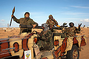 Libyan rebel fighters in a gun truck make their way towards the front lines of a battle with pro-Qaddafi forces just outside the coastal town of Bin Jawwad. Rebels fought pro-Qaddafi forces there throughout the day as they tried to regain control the town from government forces that seized the town overnight.