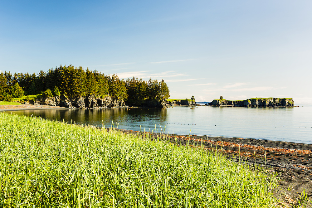 Clear skies and still waters in a small cove within Chiniak Bay on Kodiak Island in Southwestern Alaska. Summer. Morning.