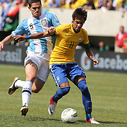 Neymar, Brazil, is challenged by Fernando Gago, Argentina, during the Brazil V Argentina International Football Friendly match at MetLife Stadium, East Rutherford, New Jersey, USA. 9th June 2012. Photo Tim Clayton