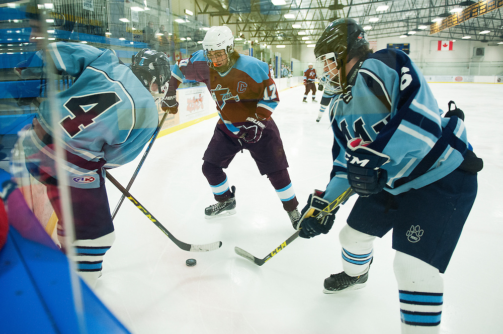 North Country's Hnery Delabruere (17) battles for the puck with MMU's Kyle Wright (4) and Justin Pond (6) during the boys hockey game between North Country and Mount Mansfield at the Essex Skating Facility on Wednesday night January 6, 2016 in Essex. (BRIAN JENKINS/for the FREE PRESS)