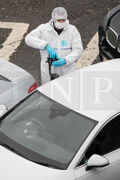 © Licensed to London News Pictures. 03/01/2017. Huddersfield, UK. Forensic scenes of crime officer photographing a bullet riddled silver Audi car at the slip road at Junction 24 of the M62 motorway in Huddersfield . West Yorkshire police have announced a man has died following the discharge of a police firearm , during what they describe as a pre-planned operation , yesterday evening (2nd January 2017) . Photo credit : Joel Goodman/LNP